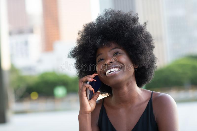 A pretty African american business woman talking on a cell phone at office building in the city royalty free stock photo