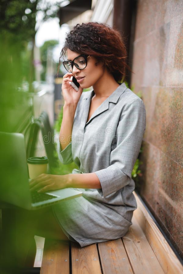 Pretty African American girl in glasses sitting on bench and talking on cellphone working on laptop. Young beautiful. Pretty African American girl in glasses royalty free stock photo