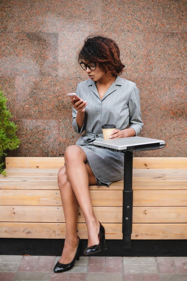 Pretty African American girl in glasses sitting on bench and using her cellphone with coffee in hand. Lady with dark. Pretty African American girl in glasses royalty free stock image