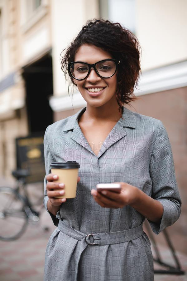Pretty African American girl in glasses standing on street with cellphone and coffee in hands while joyfully looking in. Camera. Portrait of lady with dark royalty free stock photos