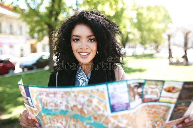 Pretty African American girl joyfully looking in camera with map in hands. Cool girl standing on street and searching. Right way on map. Portrait of smiling royalty free stock photos