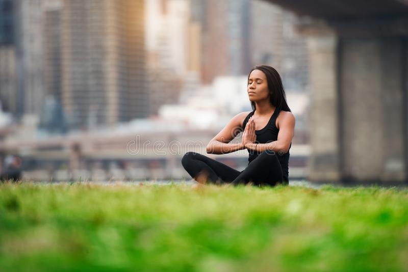 Pretty african american woman sitting on green grass doing yoga in New York City park royalty free stock images