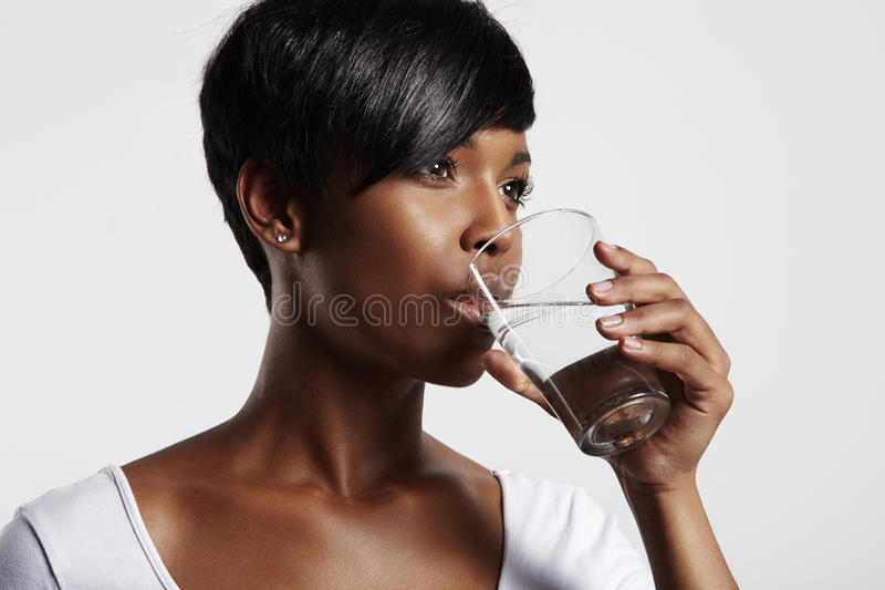 Pretty african woman drinking water stock images
