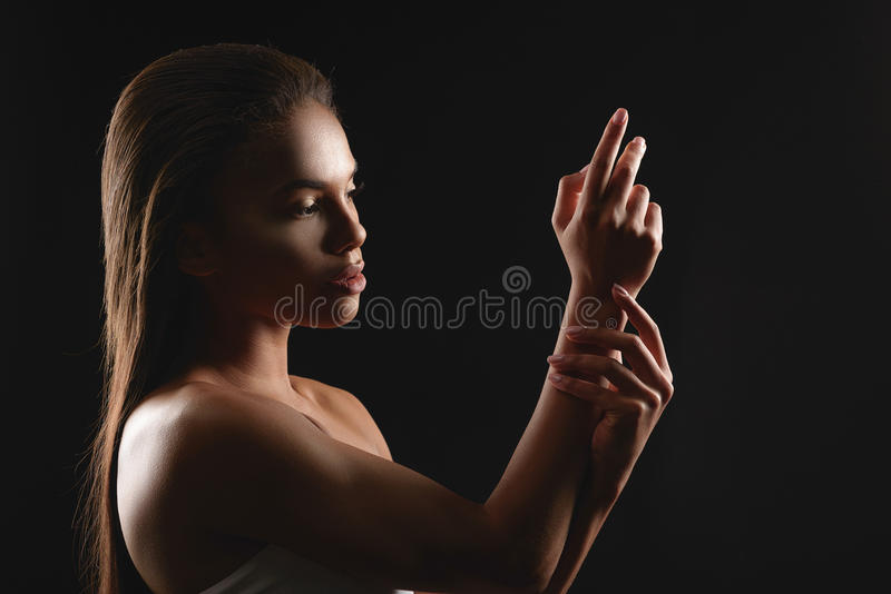 Pretty african woman likes her skin stock photography