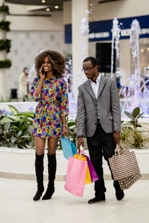 Pretty afro-american couple in a shopping mall. Woman talking on a phone and man carrying bags. stock images