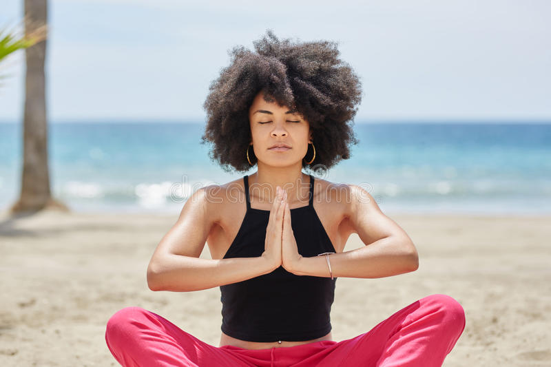 Pretty afro american woman meditating on beach royalty free stock photo