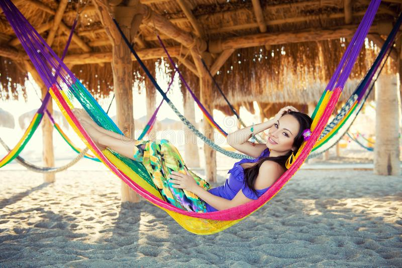 Pretty amazing cheerful young girl on the beach, lying in a hammock and smiling in a black bikini in a wide luxurious hat and royalty free stock photo