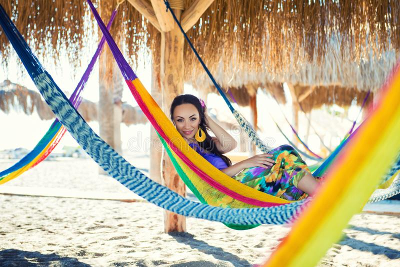 Pretty amazing cheerful young girl on the beach, lying in a hammock and smiling in a black bikini in a wide royalty free stock photos