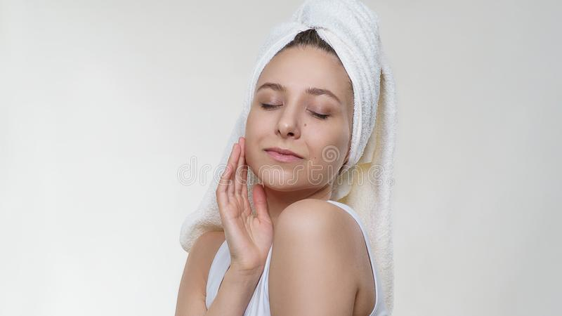 Pretty amazing woman with perfect clean skin in a towel tenderness posing with happy smile on white background royalty free stock images