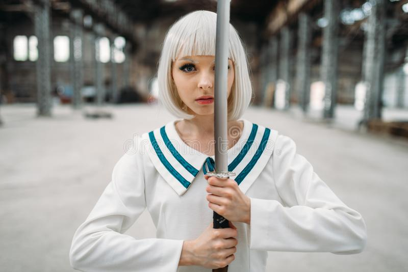 Pretty anime girl with sword, doll with blade. Pretty anime style blonde girl with sword. Cosplay fashion, asian culture, doll with blade on abandoned factory stock photo