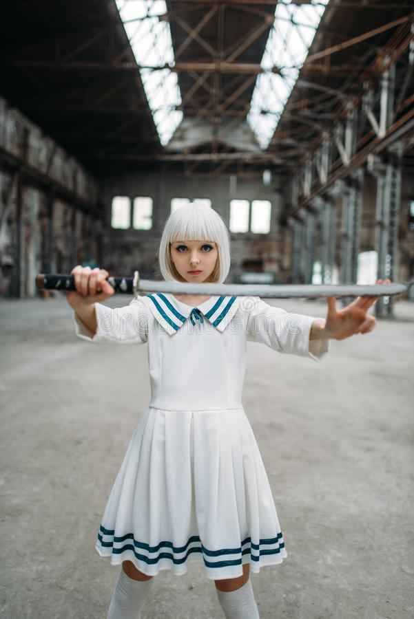 Pretty anime girl with sword, doll with blade. Pretty anime style blonde girl with sword. Cosplay fashion, asian culture, doll with blade on abandoned factory royalty free stock photo