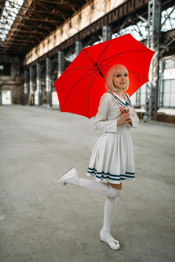 Pretty anime style blonde girl with red umbrella. Cosplay fashion, asian culture, doll in dress, cute woman with makeup in the factory shop royalty free stock images