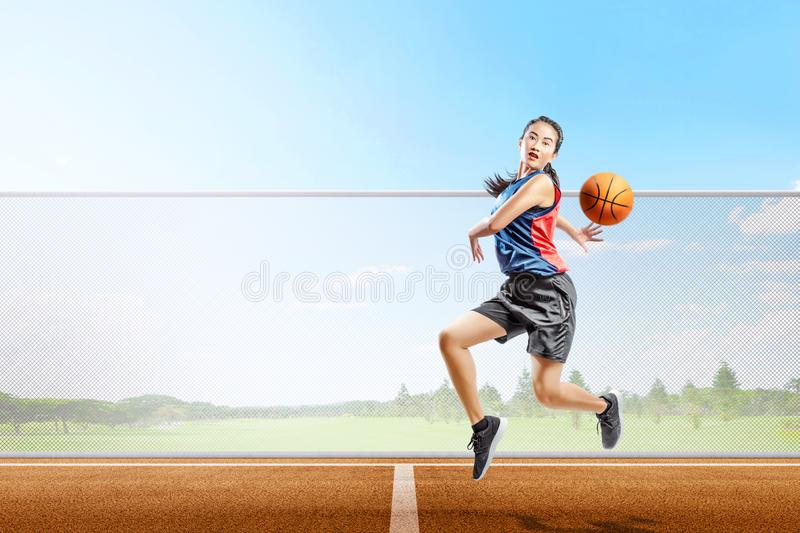 Pretty asian basketball player woman with ball in action royalty free stock images