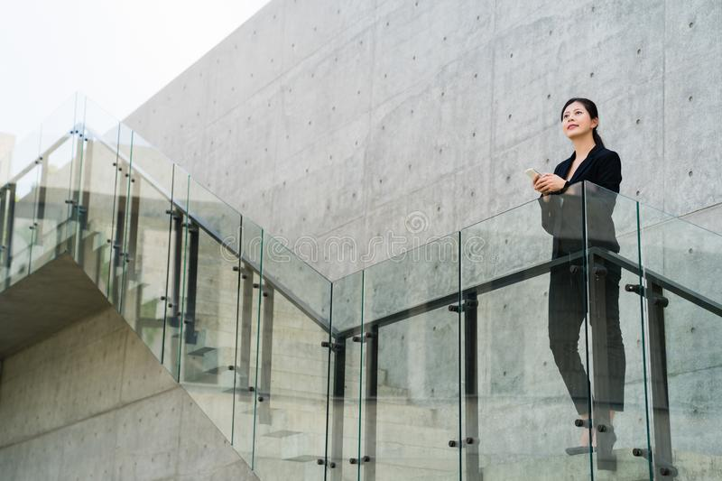 Businesswoman deliberating the state of affairs. Pretty asian businesswoman stands at the business center stairs and stares thoughtfully into the distance stock photography