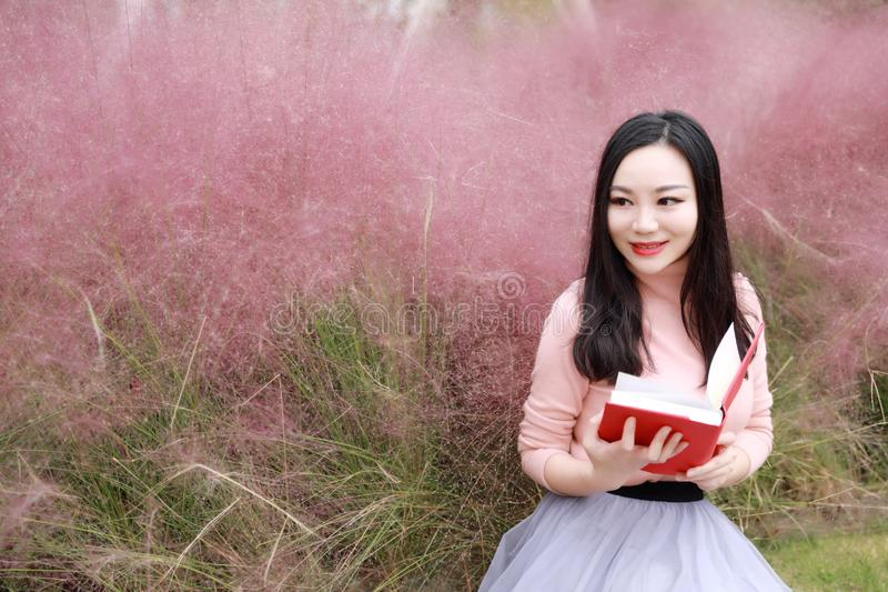Pretty Asian Chinese woman beautiful girl outdoor sit on grass lawn in a park garden feel carefree caucasian pasttime read book. Pink colour grass lawn, rose royalty free stock photos