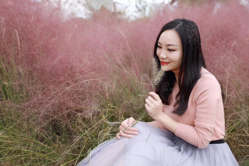 Pretty Asian Chinese woman beautiful girl selfie outdoor sit on grass lawn in a park garden feel carefree caucasian enjoy pasttime stock photography