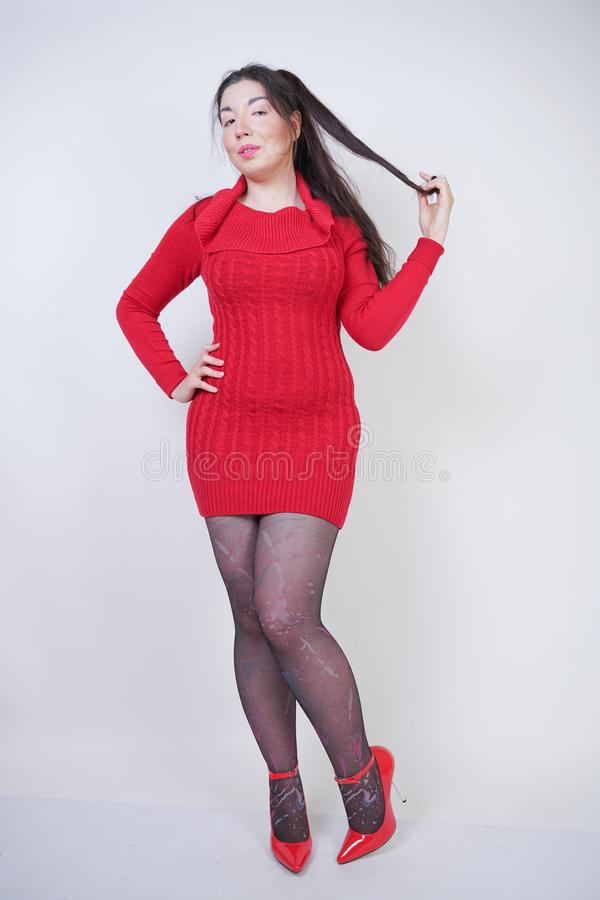 Pretty asian chubby woman posing in red knitted dress and black fashionable pantyhose on white studio background stock photos