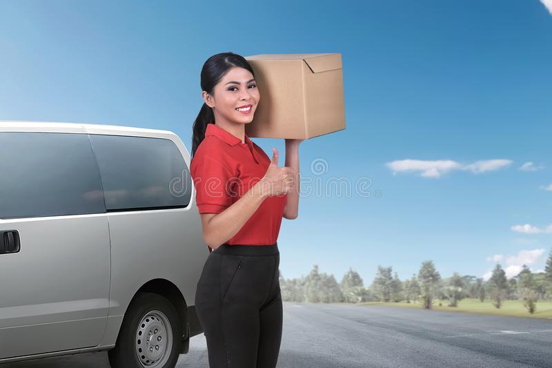 Pretty asian delivery woman standing with the package stock images