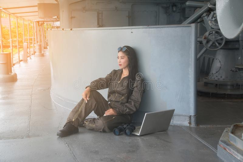 Pretty Asian female soldier sitting relax on a ship. Pretty Asian female soldier sitting relax on a ship until working finished royalty free stock photo