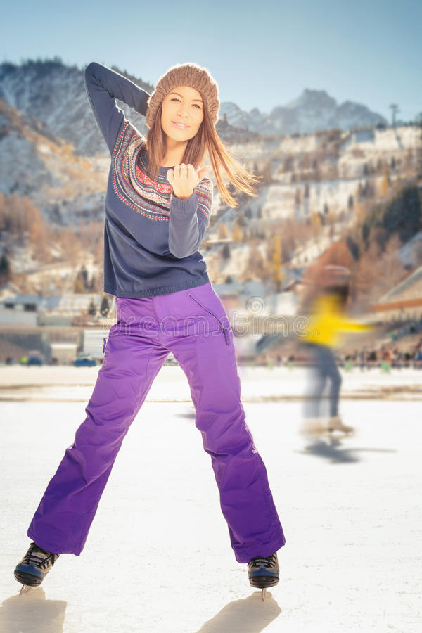 Pretty asian girl ice skating outdoor at ice rink. Young asian girl teenager sending a blow kiss and skating at the ice rink outdoor. Medeo stadium. Almaty royalty free stock image