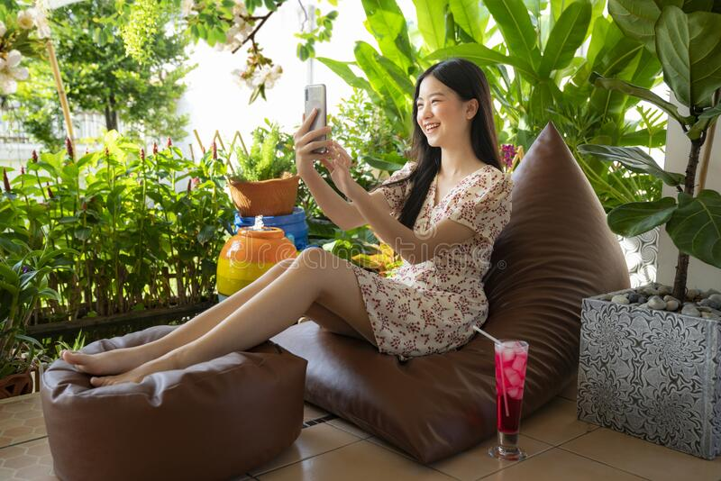 Pretty asian girl relaxing on sofa bed and browsing internet on smartphone stock photography