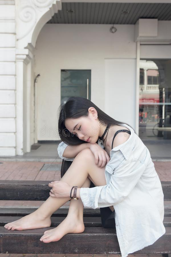 Pretty asian girl sitting on a public bench royalty free stock images