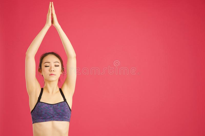Pretty asian girl stretching whilst doing aerobics and yoga in a stock image