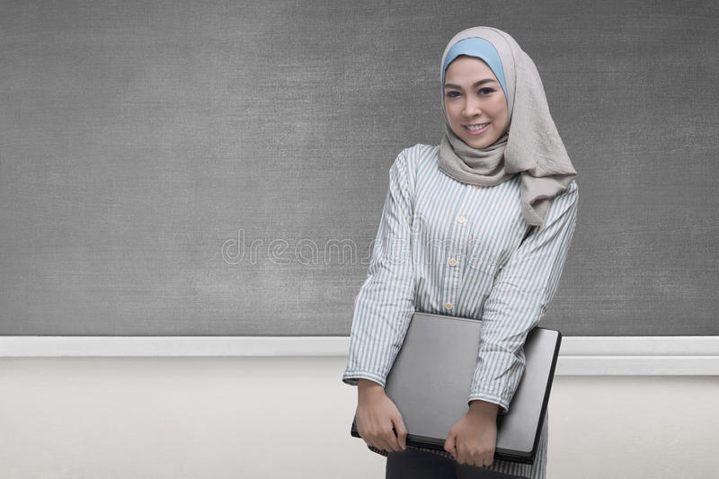 Pretty asian muslim woman holding a laptop. With blackboard background stock images