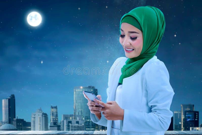 Pretty asian muslim woman using cellphone stock photos
