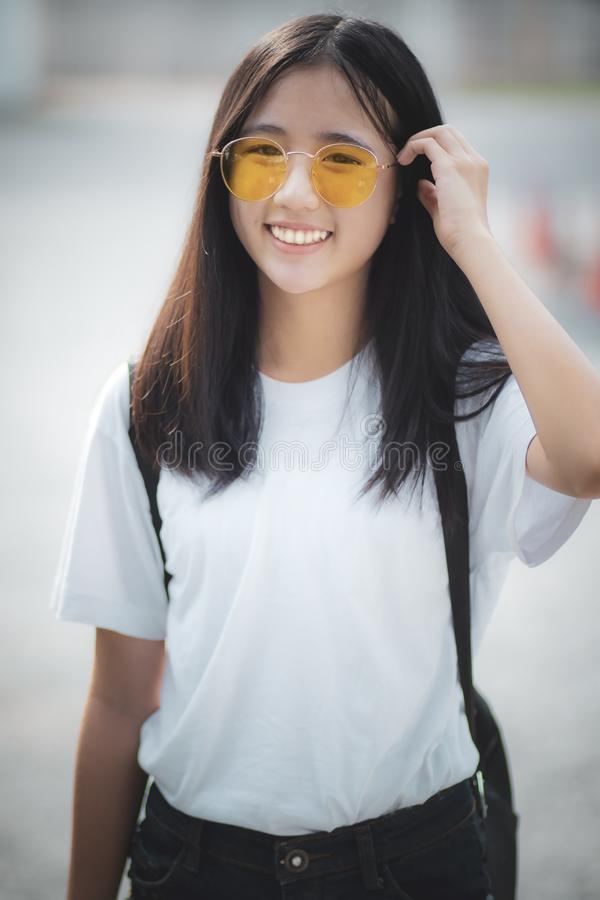 Pretty asian teenager wearing eye glasses standing outdoor stock photo