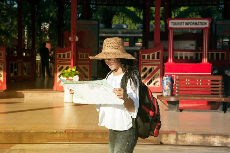 Pretty Asian traveler backpacker female looking map at railway station. royalty free stock image