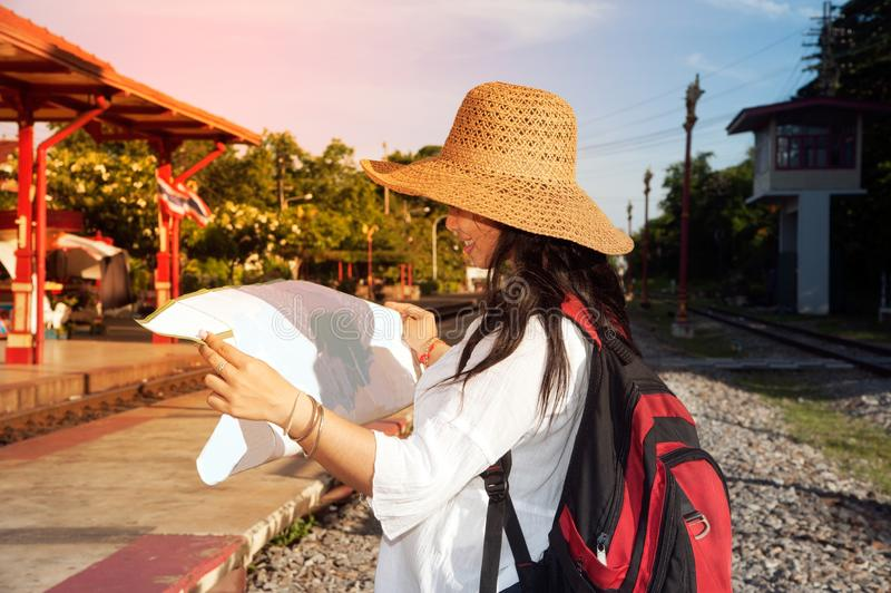 Pretty Asian traveler backpacker female looking map at railway station. royalty free stock images
