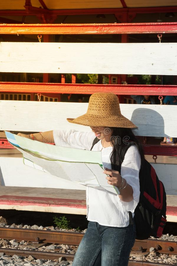 Pretty Asian traveler backpacker female looking map at railway station. royalty free stock photo