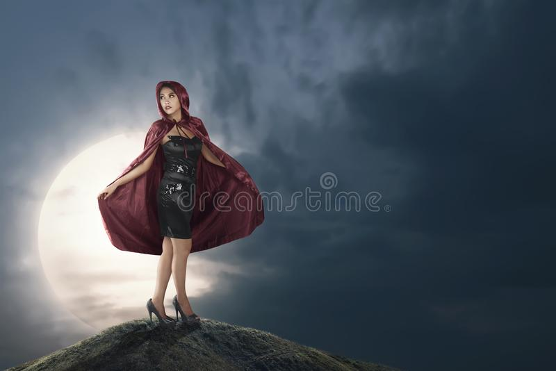 Pretty asian witch woman with red hooded cloak. On the midnight stock image