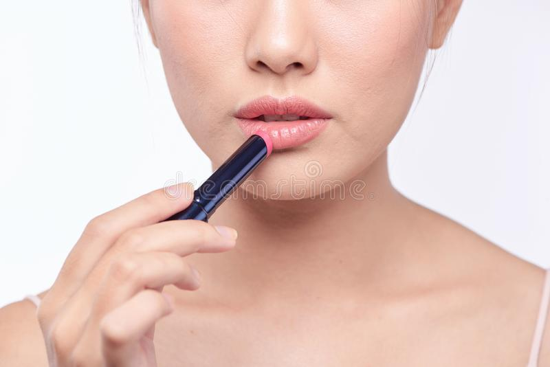 Pretty asian woman applying lipstick, isolated on white.  stock image