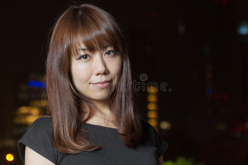 Pretty Asian woman with city light behind her royalty free stock image