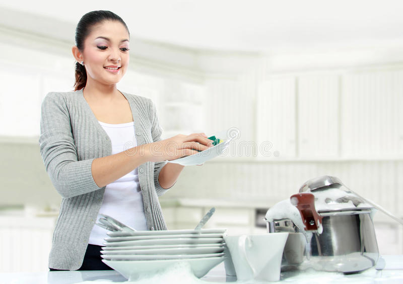 Asian woman doing house work. Pretty asian woman doing house work, washing dishes royalty free stock photography
