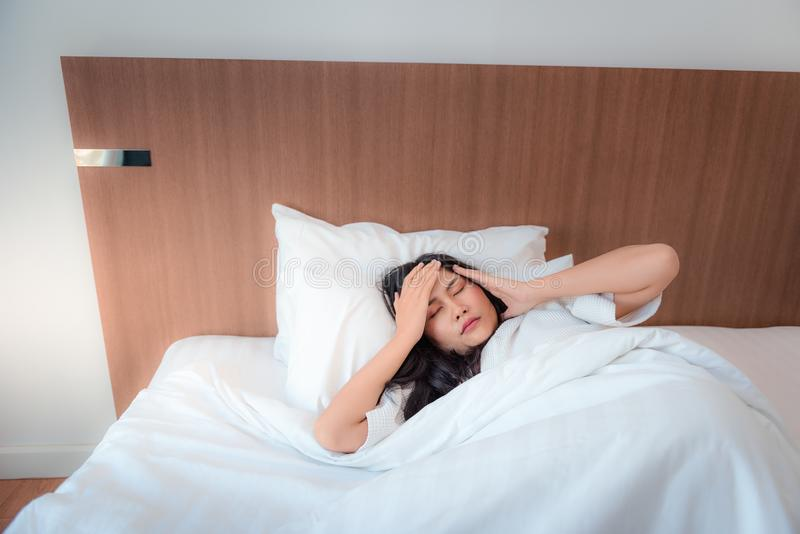 Pretty asian woman feeling headache after waked up in her's be royalty free stock photo