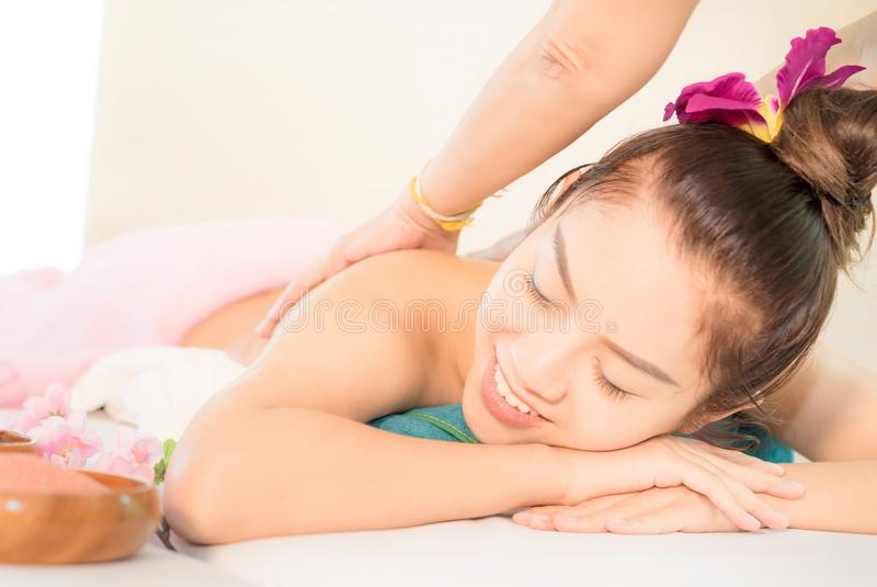 Pretty Asian woman is getting back massage in thai spa royalty free stock photos