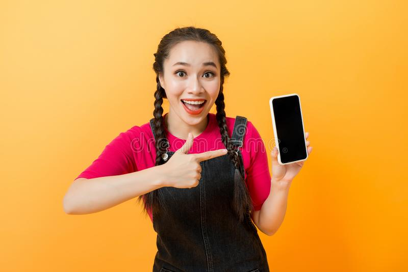 Pretty asian woman holding smartphone and pointing finger to the smartphone stock photos