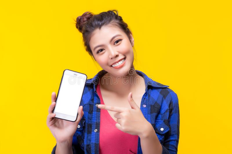 Pretty asian woman holding smartphone and pointing finger to the smartphone. Attractive beautiful young lady get satisfied and royalty free stock image