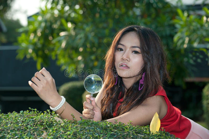 Pretty Asian woman with magnifying glass in the park . Pretty Asian woman looking with magnifying glass on the tree stock image