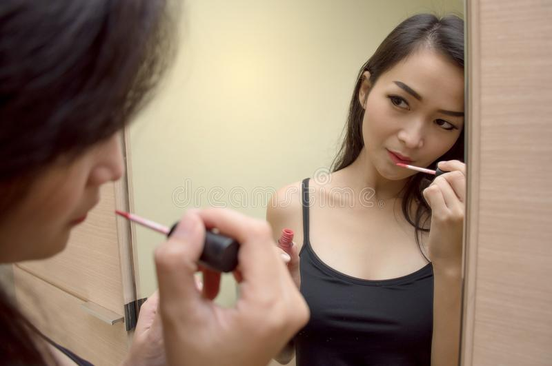 Pretty Asian woman at the mirror paints lips with red lipstick stock photos