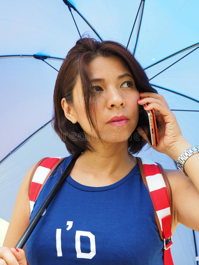 Pretty Asian woman uses smartphone royalty free stock photo
