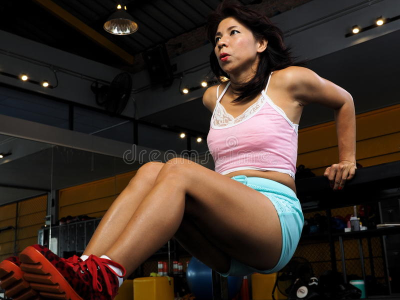 Pretty Asian woman performs bench dips at the gym. Pretty Asian woman daily works out at a gym royalty free stock images