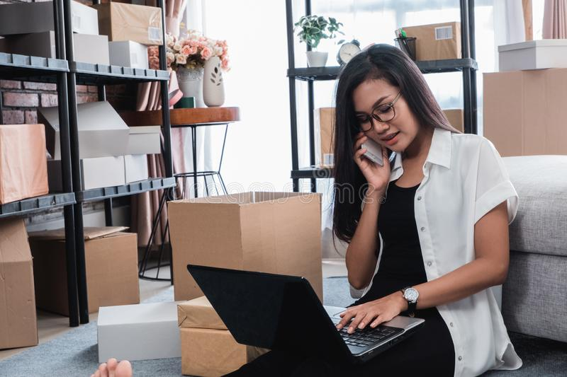 Pretty asian woman receiving online order. Busy asian woman online seller entrepreneur receiving order via phone call at home royalty free stock photography