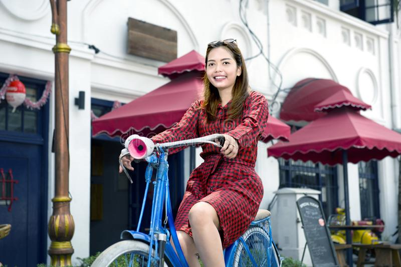 Pretty asian woman with red clothes on the bikes. In the city royalty free stock images