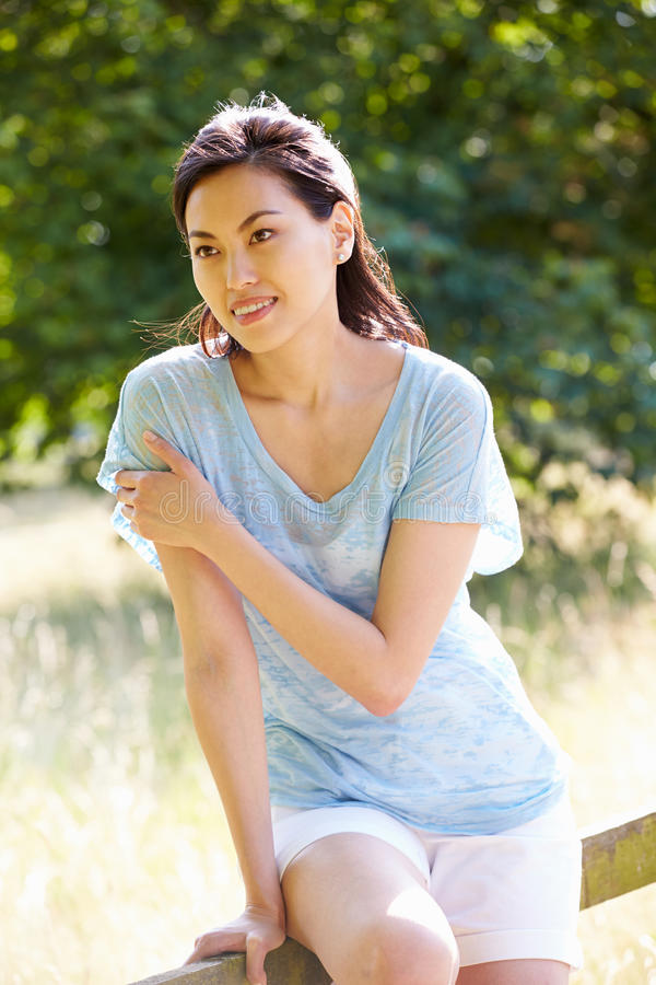 Pretty Asian Woman Sitting On Fence In Countryside stock photo
