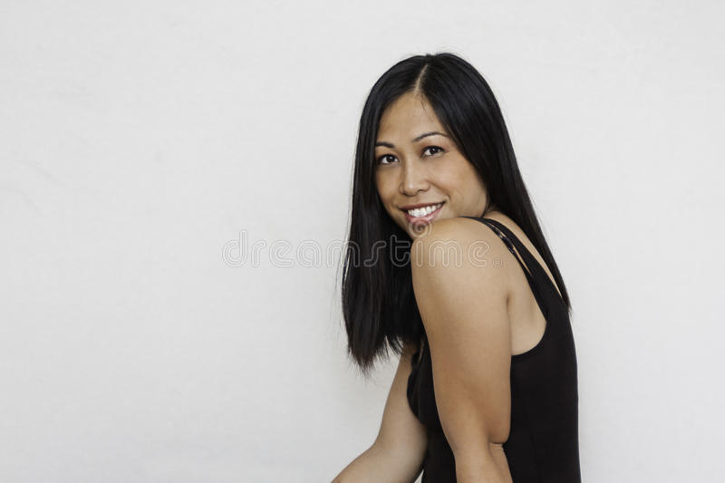 Pretty Asian woman smiling. Young, pretty Asian woman has direct eye contact with camera as she smiles. Model wears black tank top. Background is off-white royalty free stock photography