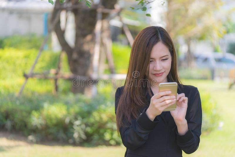 Pretty asian woman texting on mobile in city park royalty free stock images